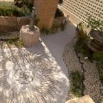 「ここから地域の皆様に開放されたコモンスペースを作り上げたい」というお施主様のお気持ちを表現する為に既存瓦の裁断で「マツの実」をイメージし舗地を作り上げた。既存の灯籠や新たに作られた井戸が設置され非常用水としての活用も考えられている。